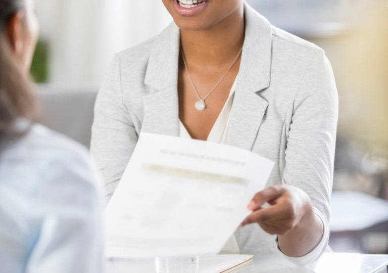 Job candidate hands resume to interviewer